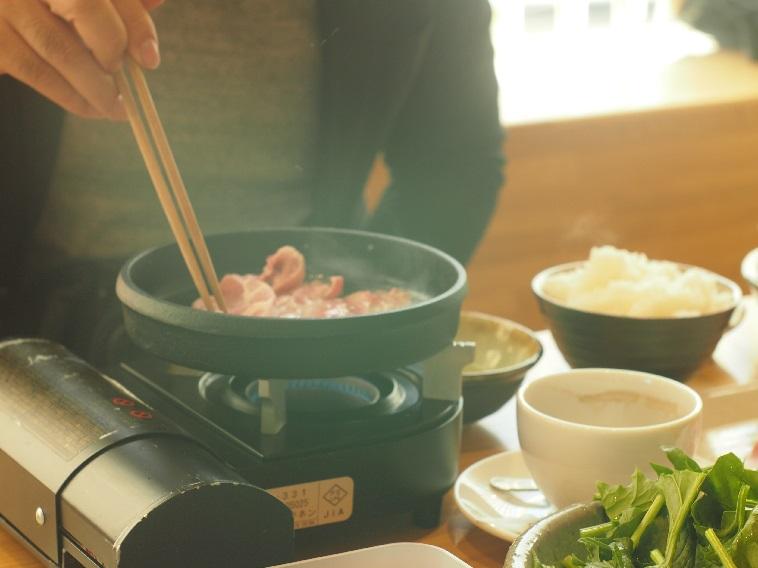 【写真】お客さんは一人一人席に運ばれるコンロの上で肉を温める。ご飯や飲み物もセットにできる