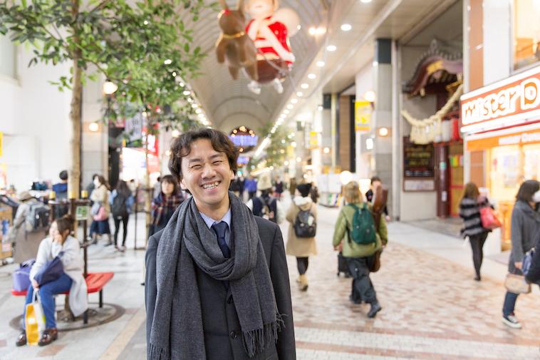 【写真】賑やかな商店街で笑顔で立っているたんのともふみさん