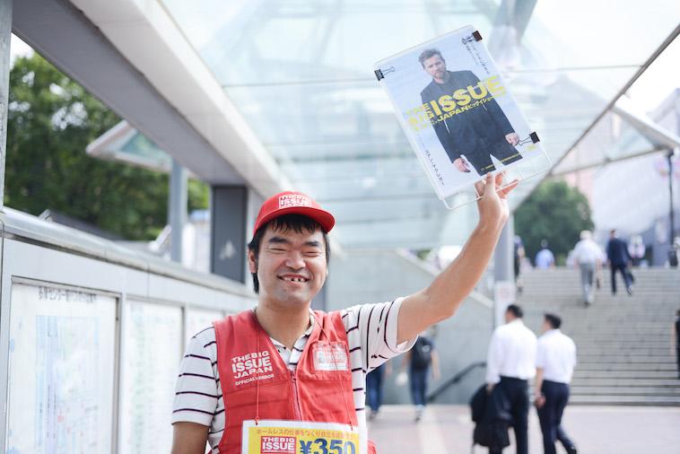 【写真】路上でビッグイシューの雑誌を高々と掲げているホームレスの方