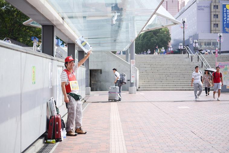 【写真】多摩センター駅前の路上でビッグイシューを掲げるやましたさん
