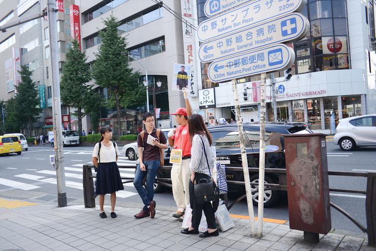 【写真】路上で高くビッグイシューを掲げる山崎さんとライターのにしやまたけしさん、くどうみずほ