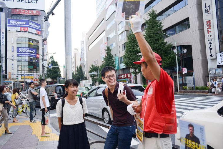 【写真】路上で高々とビッグイシューを掲げている山崎さんとライターのにしやまたけしさん