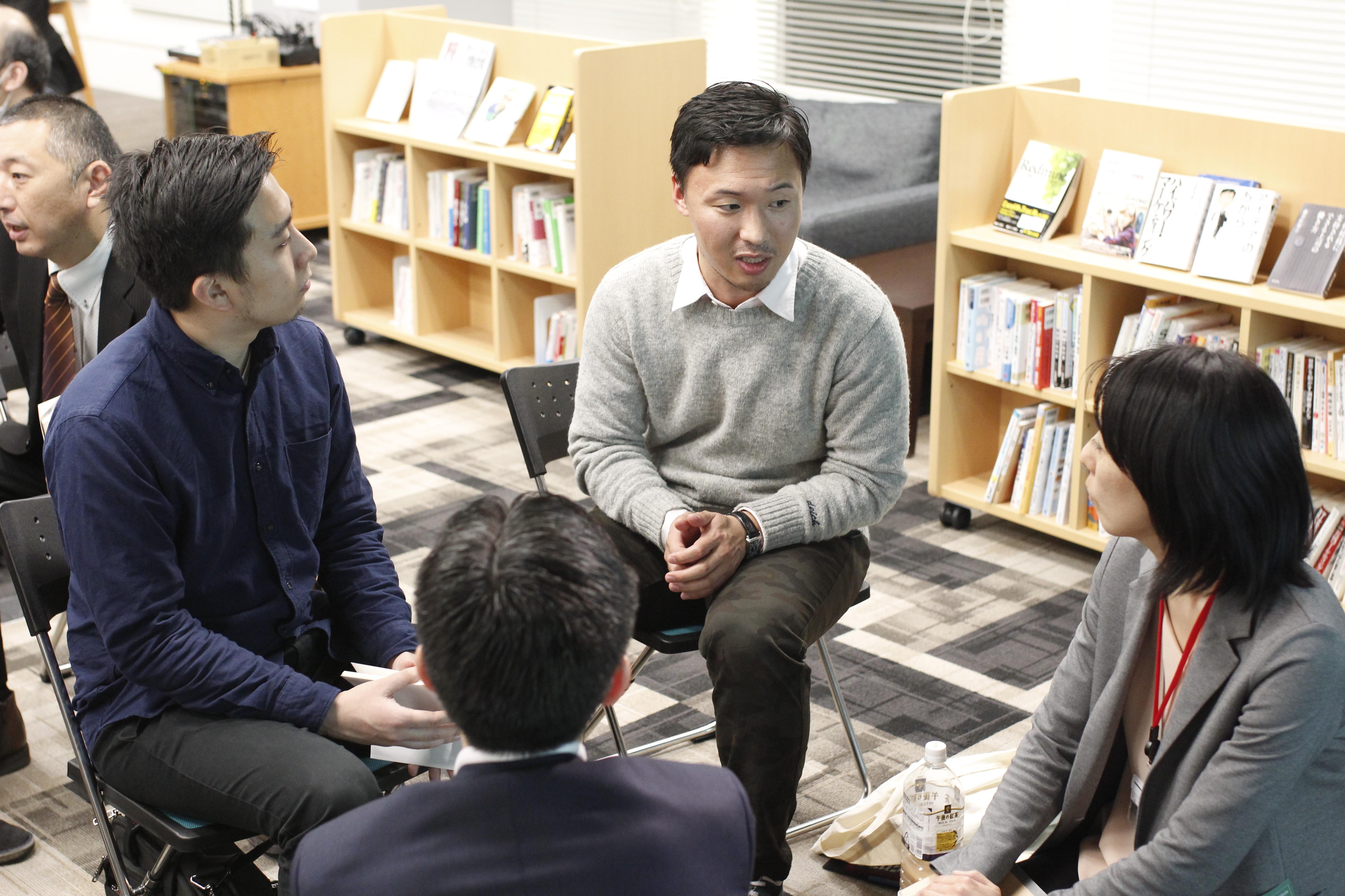 【写真】4人組になった参加者らが、真剣な表情で話している