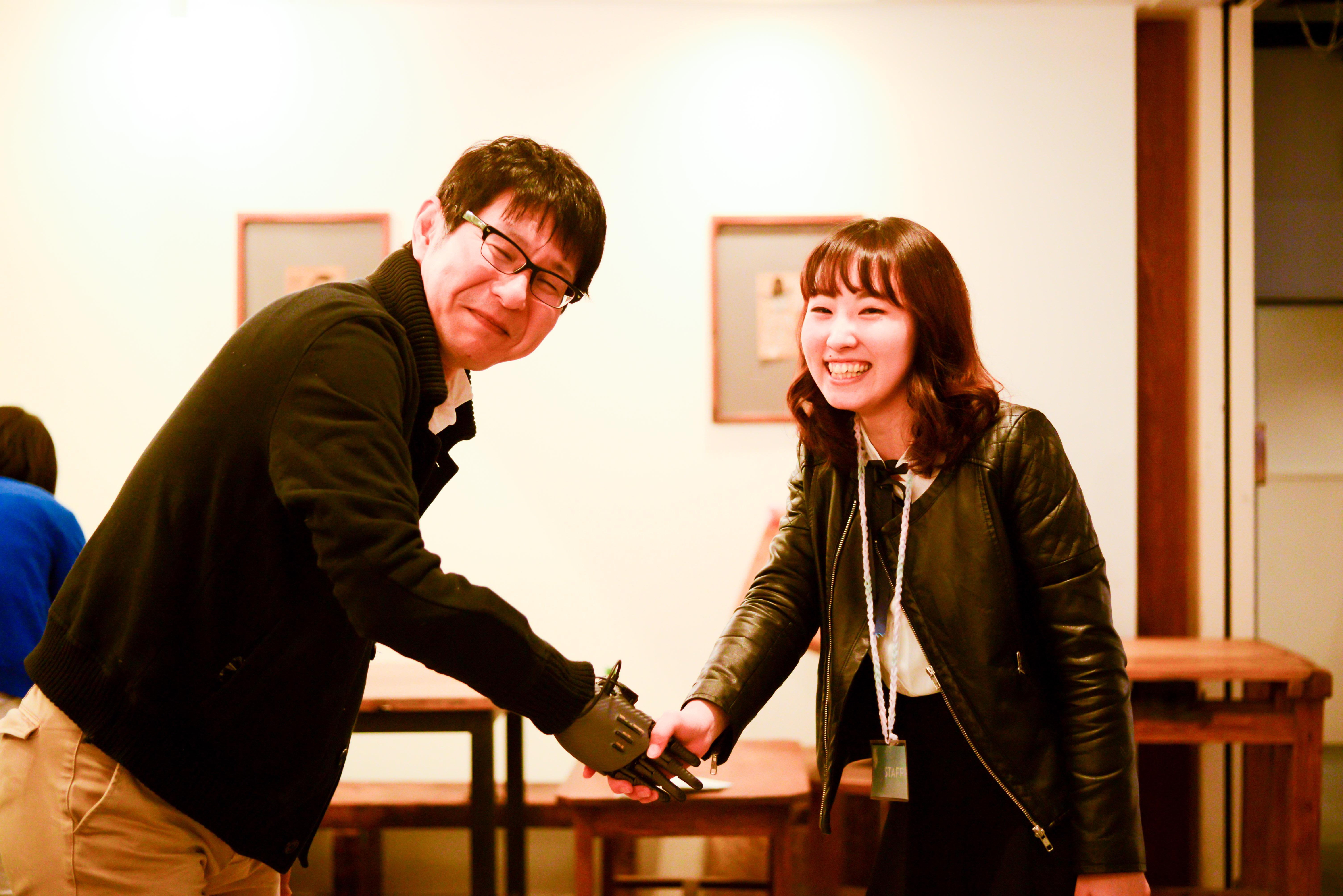 【写真】参加者と義手で握手する、笑顔の森川さん
