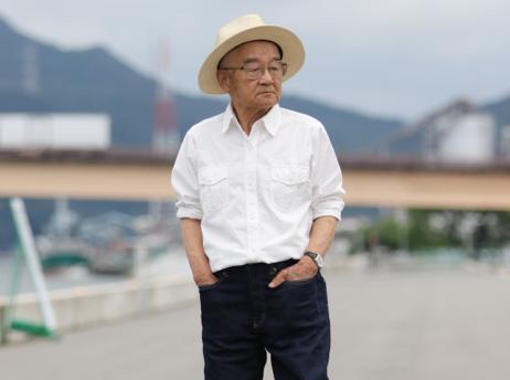 【写真】ジーンズパンツを履き、颯爽と歩く高齢者の男性。