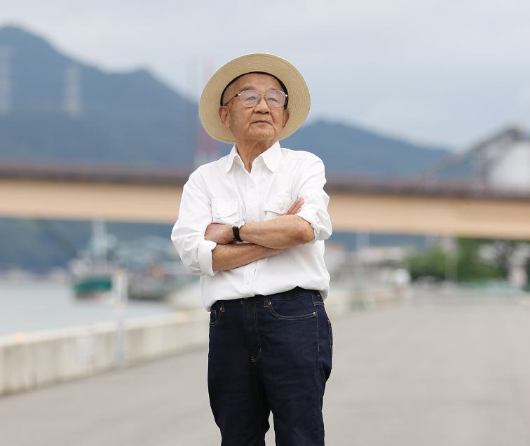 【写真】ジーンズパンツに身を包み、遠くを見つめて佇む高齢者の男性。