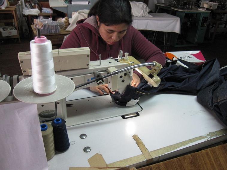 【写真】ミシンをを使い、真剣な眼差しでジーンズを縫う女性。