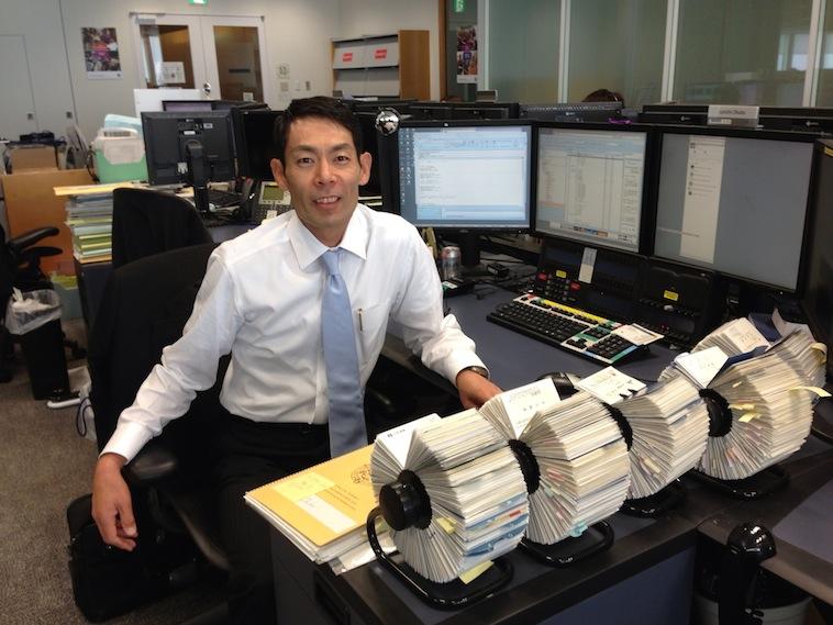【写真】会社の机に座り、ネクタイをしててこちらに笑顔を向けるおおくぼさん。