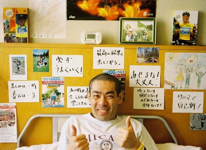 【写真】たくさんのメッセージと写真の前で微笑む、おおくぼじゅんいちさん