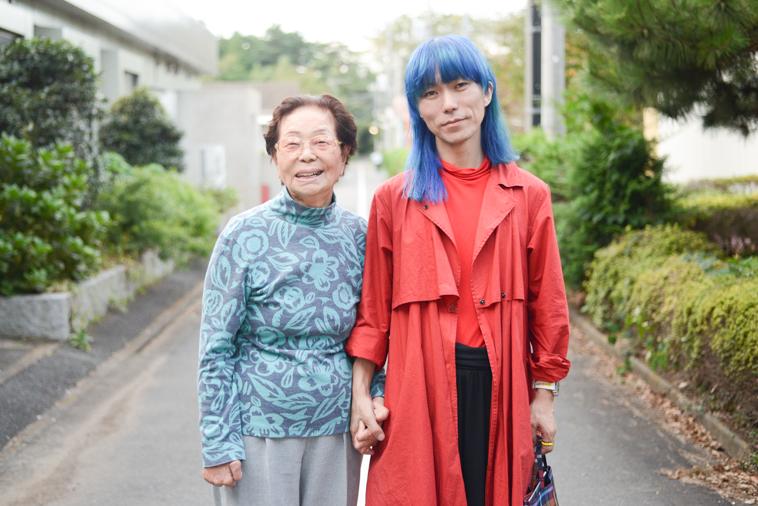【写真】手を繋いで街道に笑顔で立っているまきさんとつるたたかふみさん。
