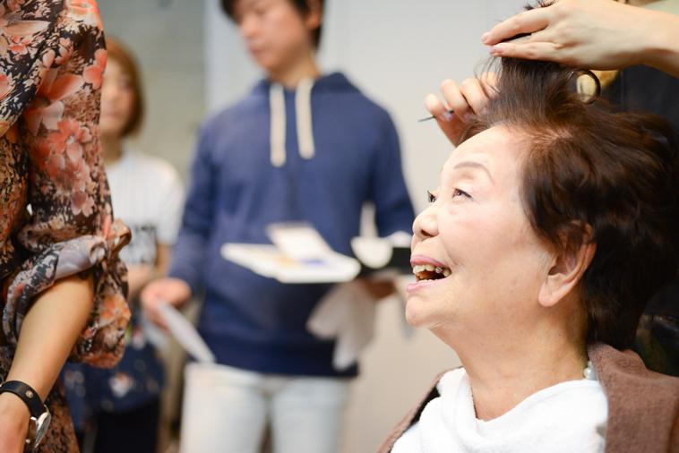 【写真】笑顔でヘアセットをしているまきさん
