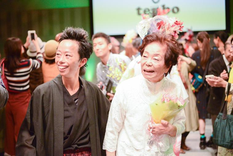 【写真】笑顔のまきさんとそうまさん。まきさんはプレゼントされた花束を持っている。