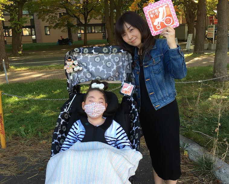 【写真】バギーマークを掲げる、まむみにょんぺっしゅ代表のみやもとさんと、車椅子に乗ったお子さん