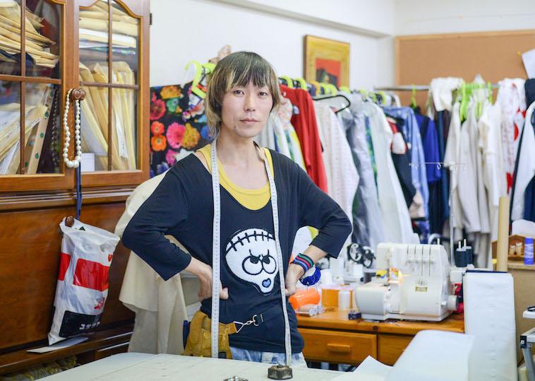 【写真】様々な服屋ミシンがあるtenboの作業所で立っているつるたたかふみさん