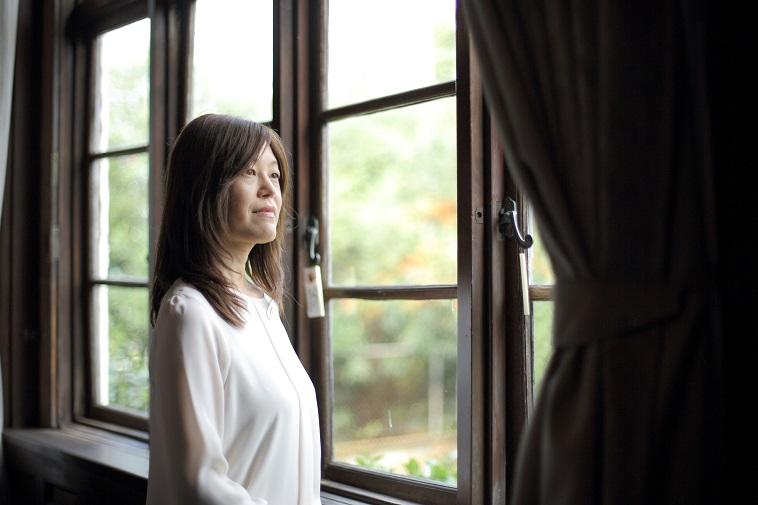 【写真】ロングのウィッグをつけ、窓から外を眺めるさいとうじゅんこさん