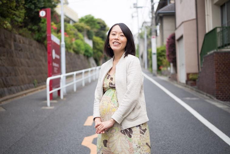 【写真】街道で笑顔で立っているにしべさおりさん