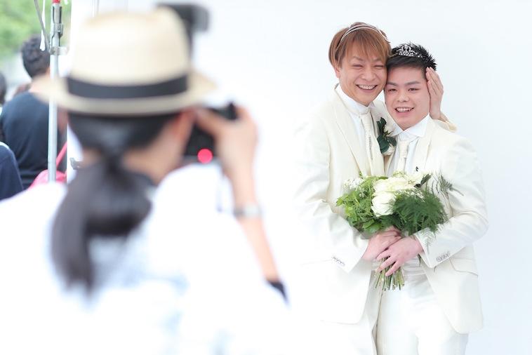 【写真】カメラの前に立ち、笑顔で写る二人の新郎。温かで幸せな空気が漂っている。