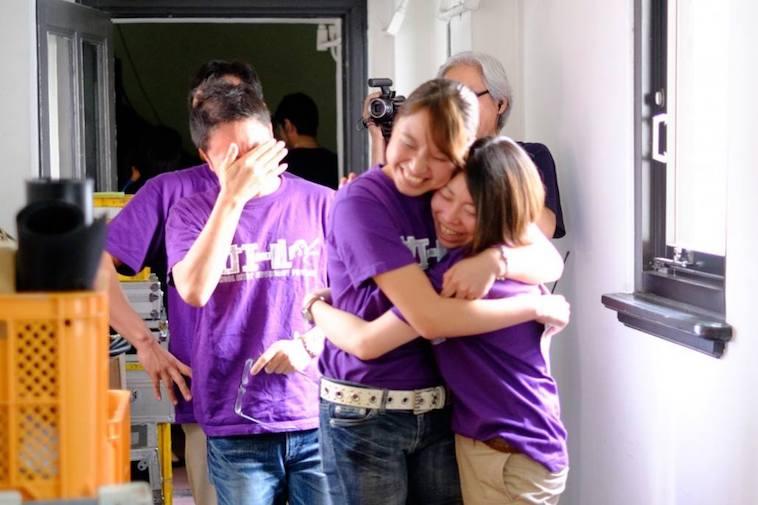 【写真】カナエールのTシャツを着たメンバーが、喜びを表現している。抱きしめ合う人や、感極まって目頭を抑える人。