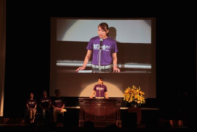 【写真】スピーチコンテストの様子。舞台の上でマイクの前に立ち、スポットライトを浴びながら堂々と話す女性。