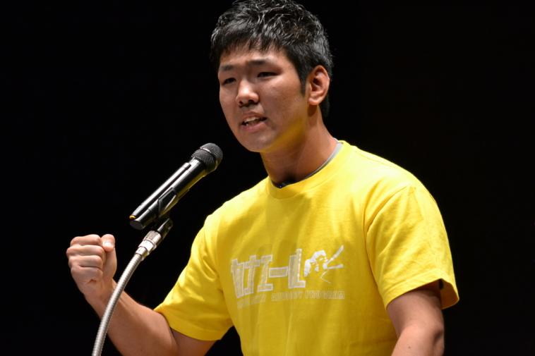 【写真】スピーチコンテストの様子。マイクの前で力強く話す男性。