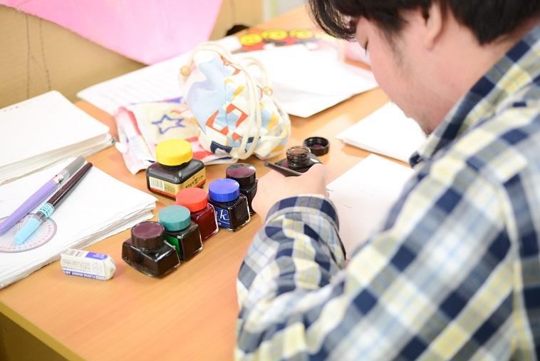 【写真】複数のインクを使い、漫画を描いている利用者。真剣な表情でペンを走らせている。