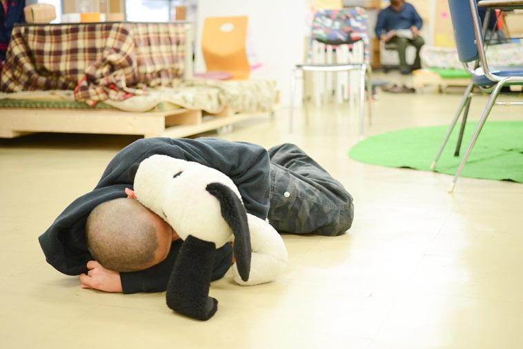 【写真】スヌーピーのぬいぐるみを抱き抱えて、床に寝そべっている利用者。心地よさそうだ。