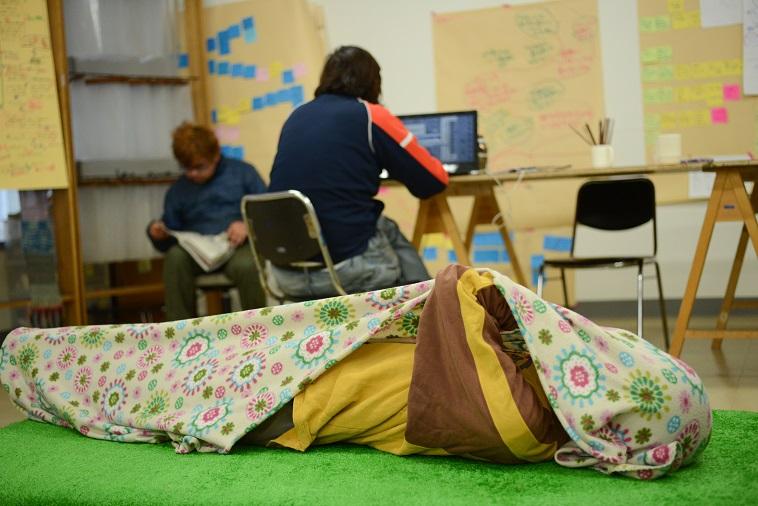 【写真】緑のマットの上に仰向けで寝転がっている利用者。ブランケットを被っている。