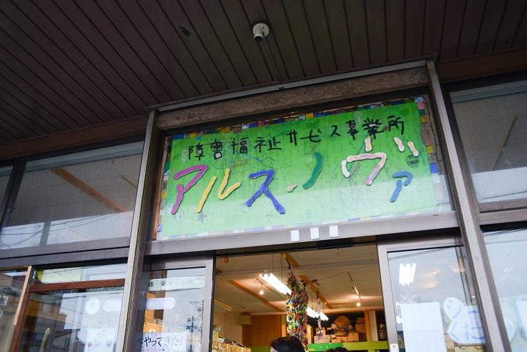 【写真】あるすのゔぁの入り口に看板が掲げてある。ピンクや黄色、青、緑、白、水色などで「あるすのゔぁ」と書かれている。