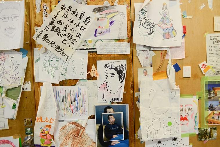 【写真】施設内のボードや壁の至るところに利用者が描いた絵や撮った写真が飾られている。それぞれタッチがバラバラで自由さを感じられる。