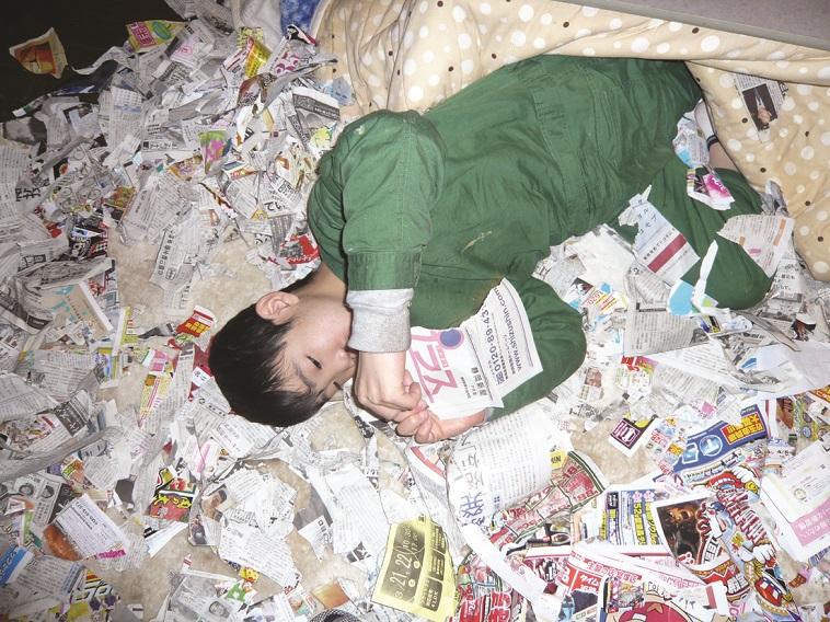 【写真】みどりさんの息子たけしくんが広告チラシや新聞紙の上に寝転がり、夢中でそれらをちぎっている。