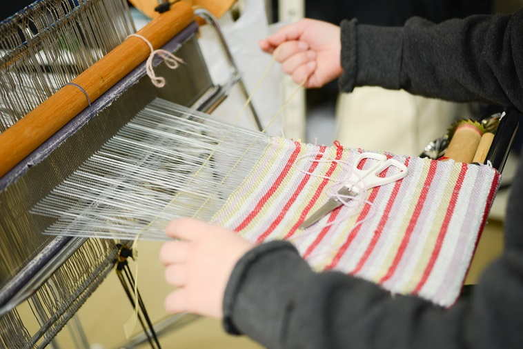 【写真】赤、白、グレー、黄色の糸を組み合わせて図柄を表現する利用者。繊細な手作業を行なっている。