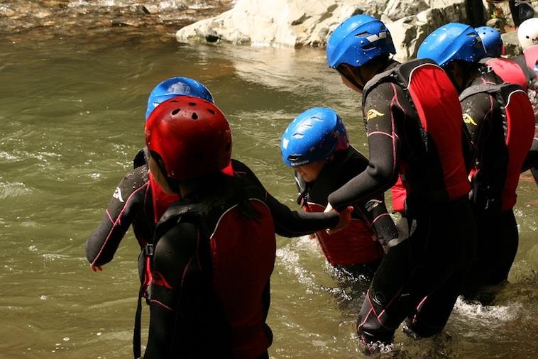 【写真】救命胴衣とヘルメットをつけて、川に足を踏み入れる子どもたち。少しの不安とワクワクした空気を感じる。