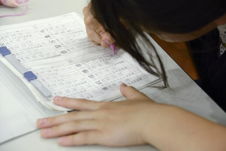 【写真】机に向かい、集中して漢字の練習を行う女の子。