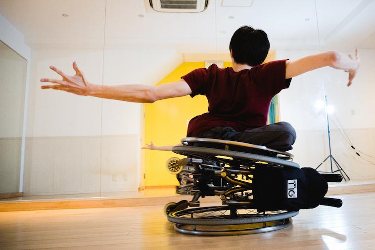 【写真】車椅子の車輪の上に乗り、腕を大きく広げるかんばらけんたさん