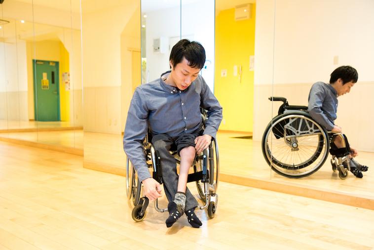 【写真】ズボンをめくって自分の足を見せてくれたかんばらけんたさん。足は成人男性と比べると非常に細い