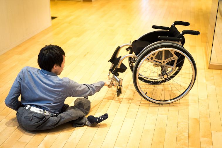 【写真】車椅子から降り、地面に座って車椅子の足の部分をもつかんばらけんたさん