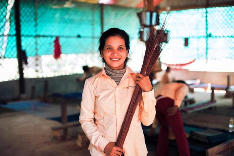 【写真】いぐさの束を抱えて、カメラに微笑みかける若い女性。