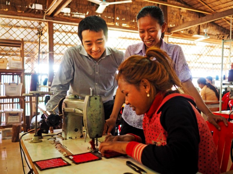 【写真】工場で作業する女性を見守るあおきさん。優しい雰囲気が流れている。