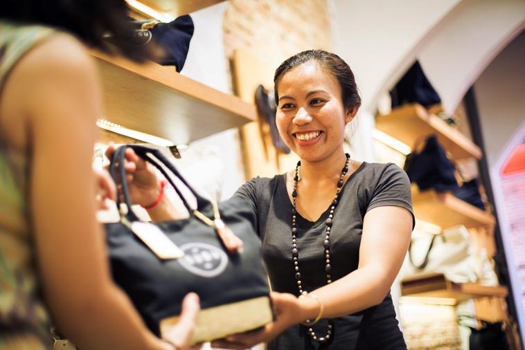 【写真】スースーの店内で、お客さんに商品を差し出すスタッフ。楽しそうな空気が伝わる。