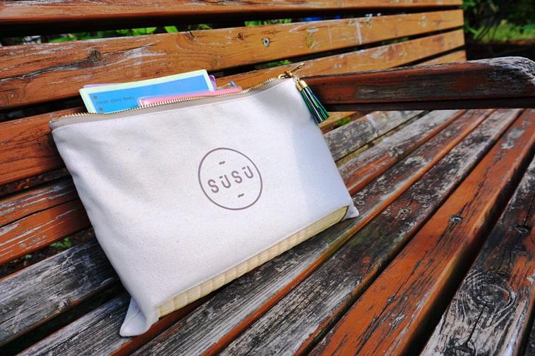 【写真】木製のベンチに置かれたスースーのクラッチバッグ。自然の空気とも相性が良いようだ。