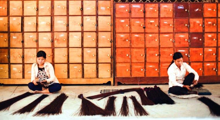 【写真】いぐさを一本一本確認する2人の女性。それぞれが集中して作業を行なっている。