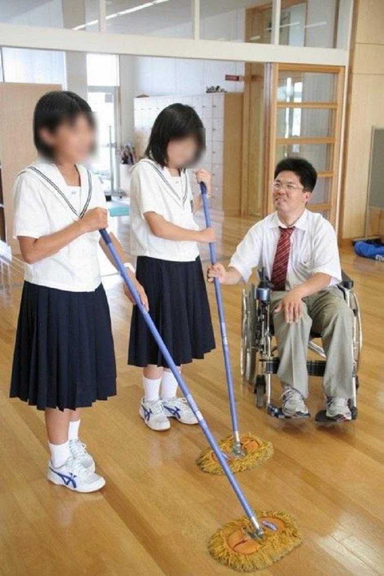 【写真】車椅子に乗った先生と掃除中の生徒が、話している。穏やかな空気が流れる。