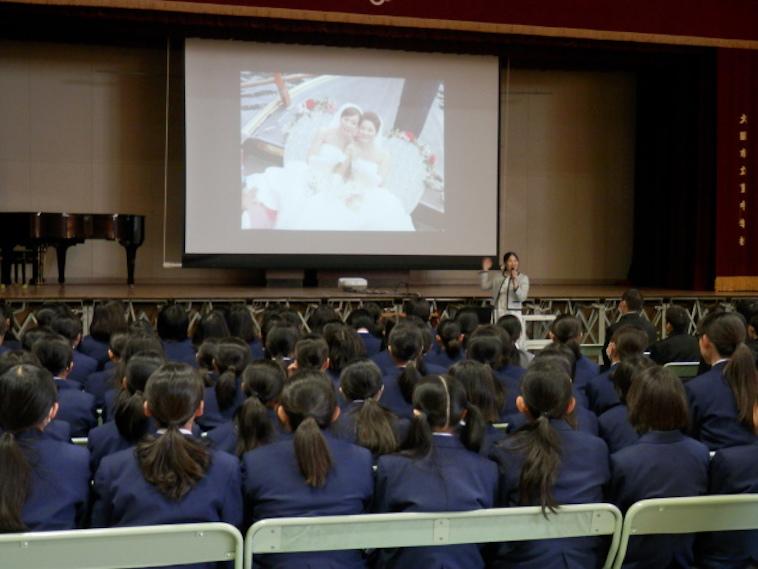 【写真】スクリーンの前に立って話すいのうえさん。生徒が注目しているのがわかる。