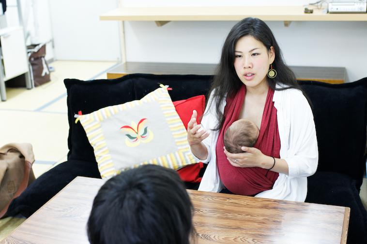 【写真】赤ちゃんを抱いて真剣な表情でインタビューに応えるはたやまれいさん