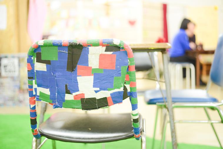 【写真】あるすのゔぁにあるパイプ椅子。黒や緑ピンク、青のテープが貼られている。