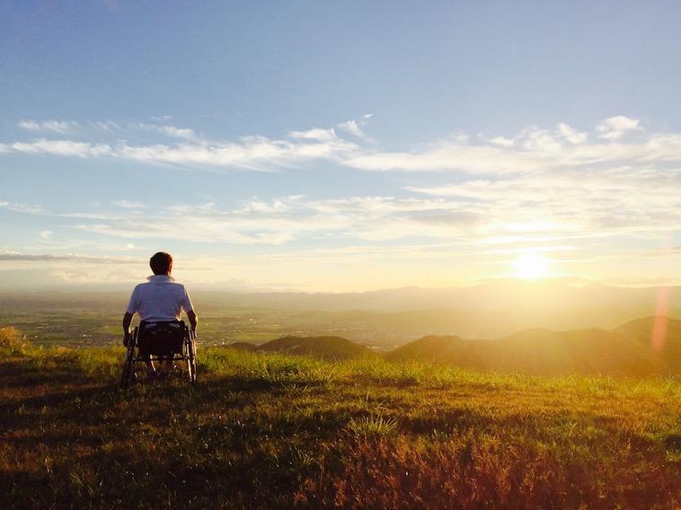 【写真】小高い山の上から夕日を眺めるかとうさん。穏やかな雰囲気が漂う。