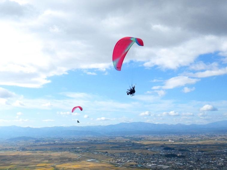 【写真】大空の中をパラグライダーで飛ぶ車椅子。天気も良く気持ちが良さそう。