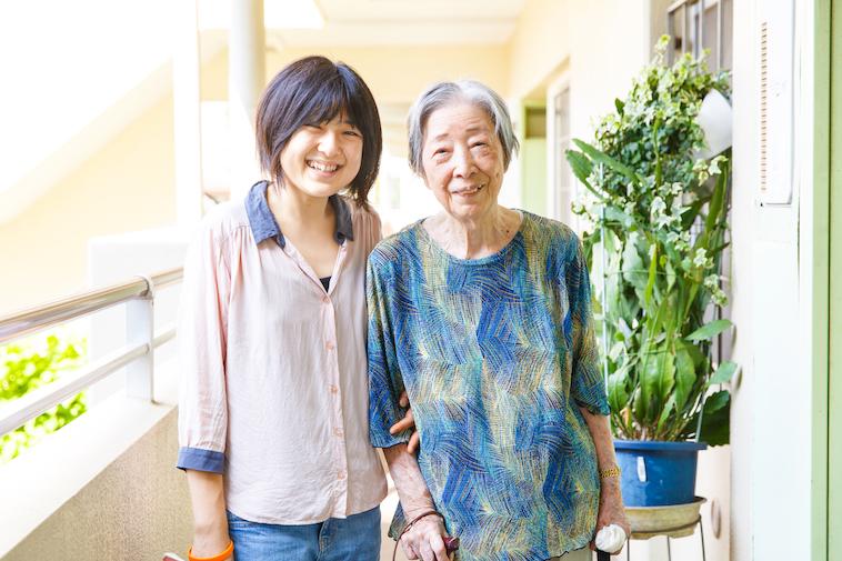 【写真】利用者の高齢女性に腕を絡めて微笑む、たかすさん