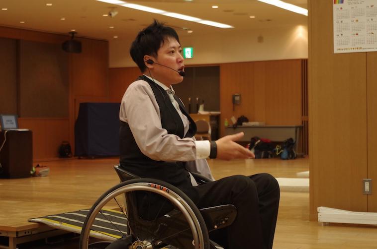【写真】ホールでマイクをつけて話すかとうさん。表情から強い思いが伝わる。