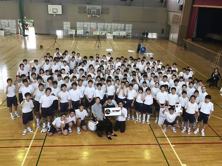 【写真】体育館で学校の子どもたちと一緒に集合写真をとる、むとうさん。明るい雰囲気が漂う。